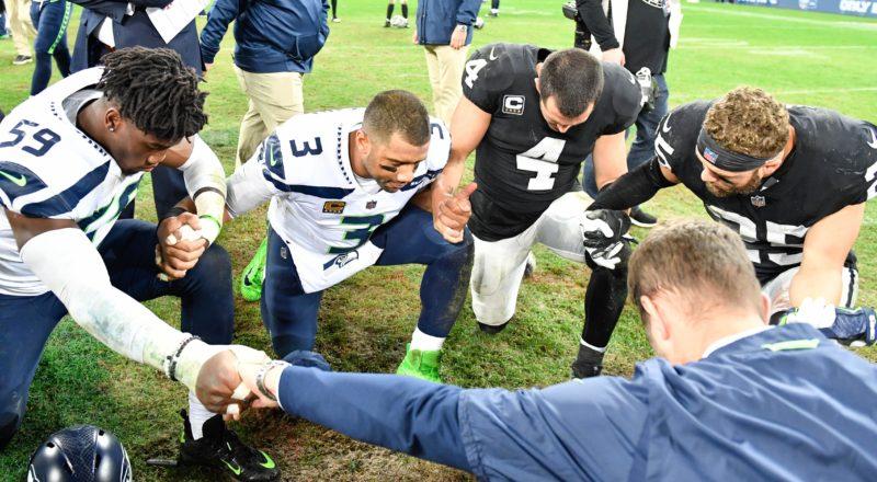 Oct 14, 2018; London, United Kingdom; Seattle Seahawks quarterback Russell Wilson (3) and Oakland Raiders quarterback Derek Carr (4) pray with teammates after an International Series game at Wembley Stadium. Mandatory Credit: Steve Flynn-USA TODAY Sports